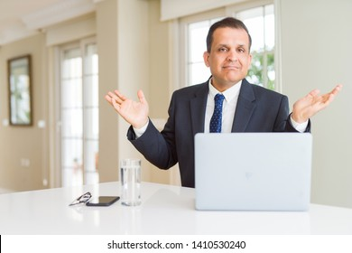 Middle age business man working with computer laptop clueless and confused expression with arms and hands raised. Doubt concept.