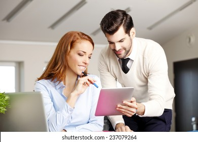 Middle age business woman giving financial advise to young sales man while working at office.