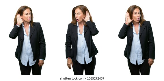 Middle age business woman holding hand near ear trying to listen to interesting news expressing communication concept and gossip over white background
