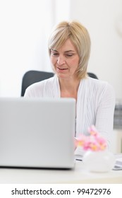 Middle age business woman working on laptop