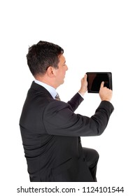 A middle age businessman in a dark suit holding up his tablet and 