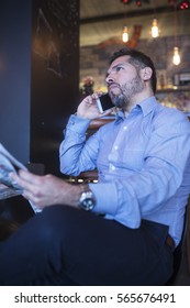 Middle age businessman reading newspapers and talking on the phone
