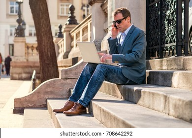 A middle age businessman siting on the stairs with a laptop while talking on the phone and wearing sunglasses