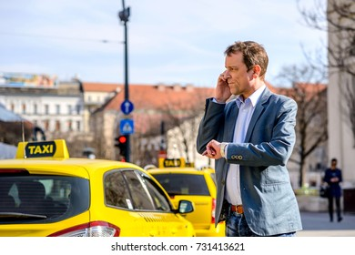 A middle age businessman waiting for an empty taxi at the taxi station while checking the time on his watch and talking on his phone
