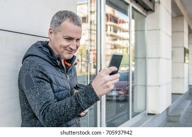 A middle age businessman walking next to the office building while using his smartphone. Casual urban professional entrepreneur using smartphone