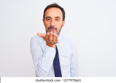 Middle age businessman wearing elegant tie standing over isolated white background looking at the camera blowing a kiss with hand on air being lovely and sexy. Love expression.