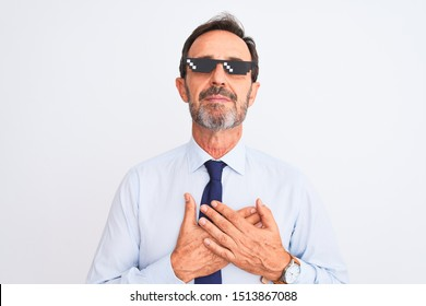 Middle age businessman wearing thug life sunglasses over isolated white background smiling with hands on chest with closed eyes and grateful gesture on face. Health concept.