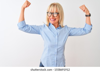 Middle age businesswoman wearing elegant shirt and glasses over isolated white background showing arms muscles smiling proud. Fitness concept.