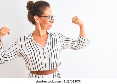 Middle age businesswoman wearing striped dress and glasses over isolated white background showing arms muscles smiling proud. Fitness concept.