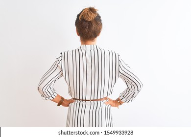 Middle age businesswoman wearing striped dress and glasses over isolated white background standing backwards looking away with arms on body