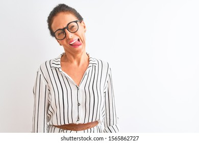 Middle age businesswoman wearing striped dress and glasses over isolated white background sticking tongue out happy with funny expression. Emotion concept.