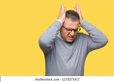 Middle age bussines arab man wearing glasses over isolated background suffering from headache desperate and stressed because pain and migraine. Hands on head.
