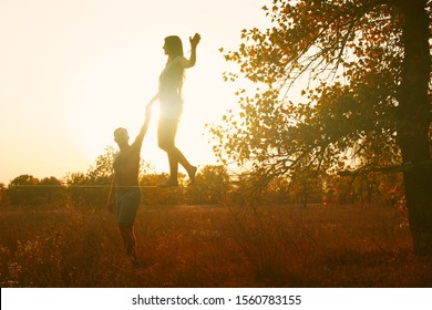 Middle age Caucasian couple slacking in a field at sunset.