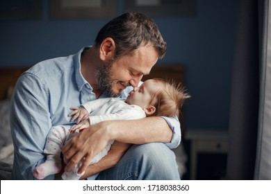 Middle age Caucasian father kissing sleeping newborn baby girl. Parent holding rocking child daughter son in hands. Authentic lifestyle parenting fatherhood moment. Single dad family home life.