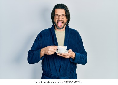 Middle age caucasian man wearing robe drinking coffee sticking tongue out happy with funny expression.