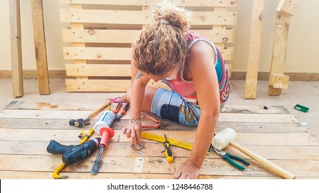 Middle age caucasian woman repairing and building furnitures using recycled wood from cargo pallets outdoor - hardware and all necessary for work leisure activity like hobby or business