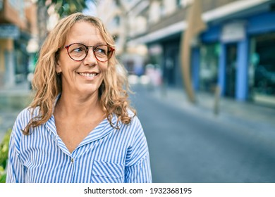 Middle age caucasian woman smiling happy standing at the city.