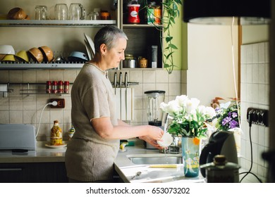 Middle age charming gray haired woman Wash dishes in the kitchen