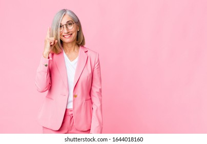 middle age cool woman feeling like a genius holding finger proudly up in the air after realizing a great idea, saying eureka against flat wall