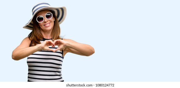 Middle age cool woman wearing summer hat and sunglasses happy showing love with hands in heart shape expressing healthy and marriage symbol isolated blue background
