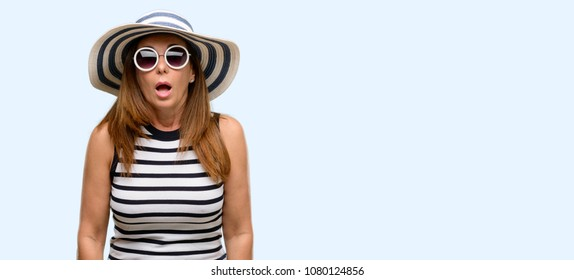 Middle age cool woman wearing summer hat and sunglasses scared in shock, expressing panic and fear isolated blue background
