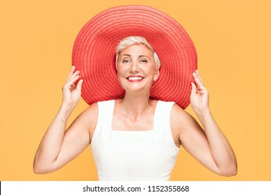 46d1cb559d5 Middle age cool woman wearing red summer hat looking at camera and smiling