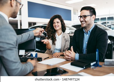 Middle age couple choosing and buying car at car showroom. Car salesman gives them car keys.