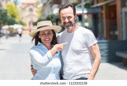 Middle age couple down the street very happy pointing with hand and finger