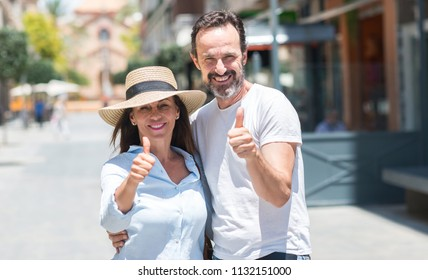 Middle age couple down the street happy with big smile doing ok sign, thumb up with fingers, excellent sign