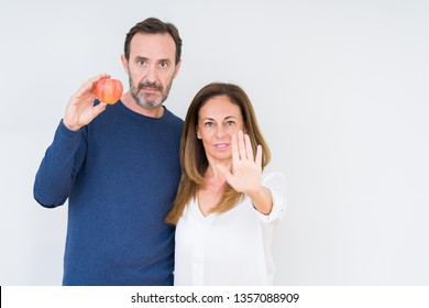 Middle age couple eating fresh apple over isolated background with open hand doing stop sign with serious and confident expression, defense gesture