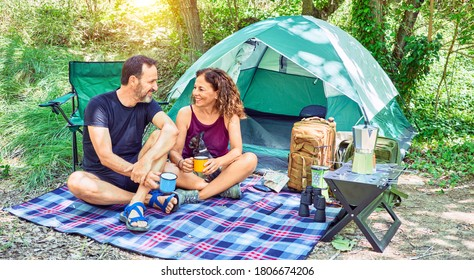 Middle age couple  of hiker drinking coffee camping at the forest.