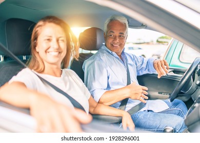 Middle age couple in love sitting inside the car going for a trip smiling happy and cheerful together