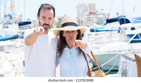 Middle age couple in marina pointing with finger to the camera and to you, hand sign, positive and confident gesture from the front