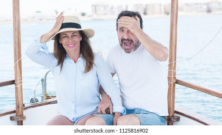 Middle age couple traveling on sailboat stressed with hand on head, shocked with shame and surprise face, angry and frustrated. Fear and upset for mistake.