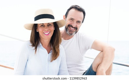 Middle age couple traveling on sailboat with a happy face standing and smiling with a confident smile showing teeth