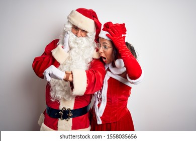 Middle age couple wearing Santa costume hugging over isolated white background Looking at the watch time worried, afraid of getting late