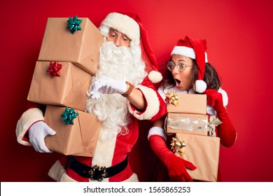 Middle age couple wearing Santa costume holding tower of gifts over isolated red background Looking at the watch time worried, afraid of getting late