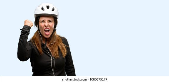 Middle age cyclist woman using earphones irritated and angry expressing negative emotion, annoyed with someone isolated blue background