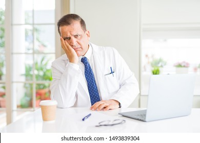 Middle age doctor man wearing white medical coat working with laptop at the clinic thinking looking tired and bored with depression problems with crossed arms.