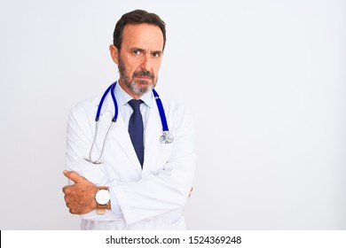 Middle age doctor man wearing coat and stethoscope standing over isolated white background skeptic and nervous, disapproving expression on face with crossed arms. Negative person.