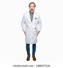 Middle age doctor men wearing medical coat afraid and shocked with surprise expression, fear and excited face.