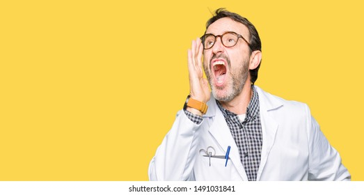 Middle age doctor men wearing medical coat shouting and screaming loud to side with hand on mouth. Communication concept.