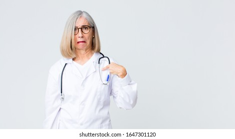 middle age doctor woman feeling confused, puzzled and insecure, pointing to self wondering and asking who, me?