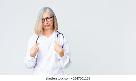 middle age doctor woman pointing to self with a confused and quizzical look, shocked and surprised to be chosen