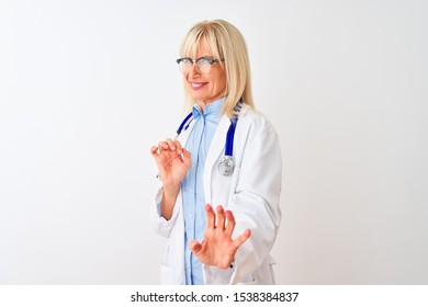 Middle age doctor woman wearing glasses and stethoscope over isolated white background disgusted expression, displeased and fearful doing disgust face because aversion reaction. With hands raised