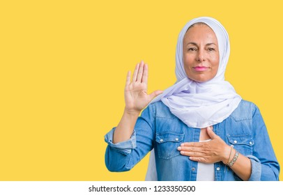 Middle age eastern arab woman wearing arabian hijab over isolated background Swearing with hand on chest and open palm, making a loyalty promise oath