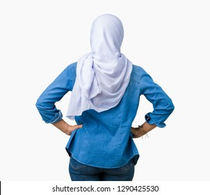 Middle age eastern arab woman wearing arabian hijab over isolated background standing backwards looking away with arms on body