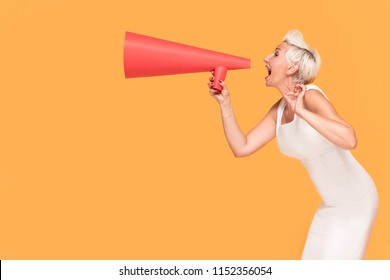 Middle age elegant woman shouting loud by red megaphone, smiling, looking at camera. Lady expressing positive concept on orange studio background.
