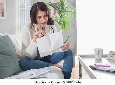 Middle age family woman working out home expenses in living room, looking at bills and doing finances, indoors. Financial living costs, home accounts, monthly outgoings. Economics lifestyle.