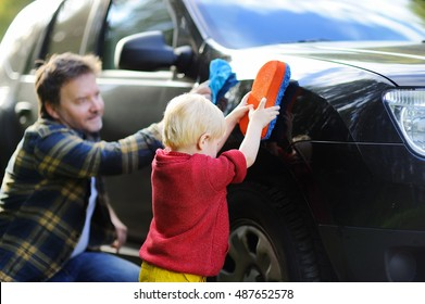 Middle age father with his toddler son washing car